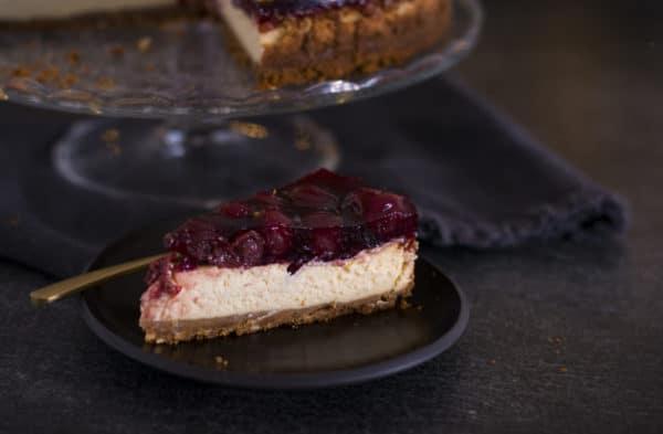 Kuchenstück von einem Christmas Cheesecake und dahinter der angeschnittene Käsekuchen auf einer Tortenplatte