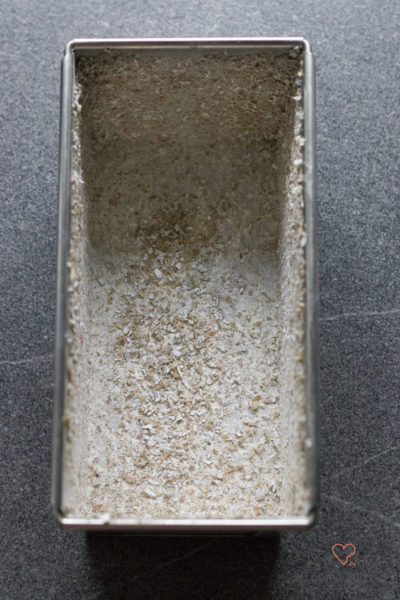 Kastenform mit Schrot ausgestreut für ein kerniges Vollkornbrot.