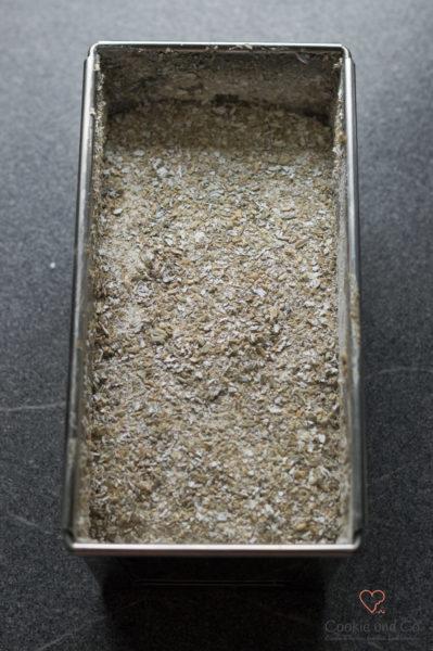 Teig für ein kerniges Vollkornbrot in einer Kastenform, bestreut mit feinem Schrot.