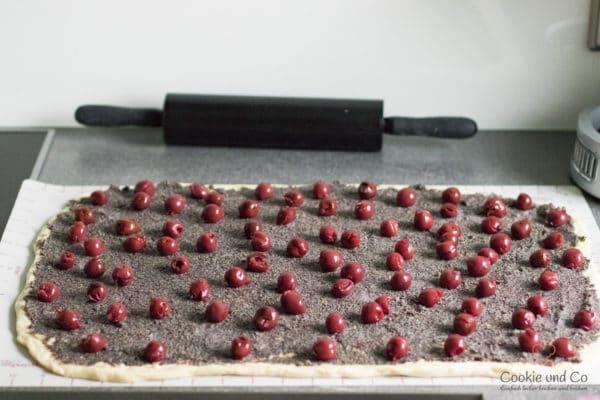 Ausgerollter Teig mit Mohnfüllung und Kirschen für Mohn-Schnecken mit Marzipan.