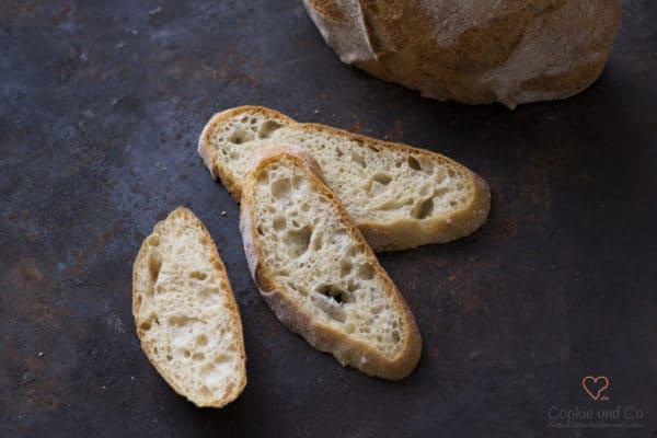 Mediterranes No Knead Bread in Scheiben auf einem alten Backblech.