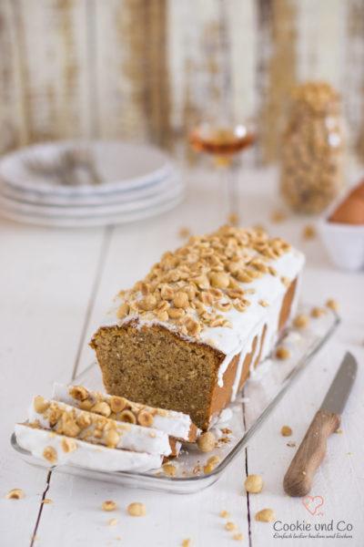Nusskuchen, dekoriert mit Zucker und Haselnüssen auf einer Kuchenplatte.