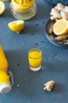 Zitronen-Ingwer-Trunk mit Kurkuma in einem Glas und Flaschen