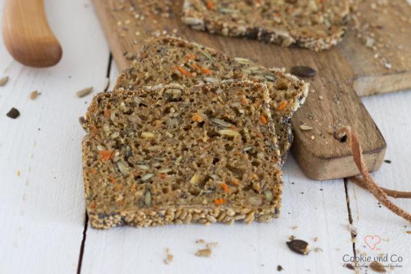 Dinkel-Möhren-Vollkornbrot auf einem Holzbrett in Scheiben geschnitten.