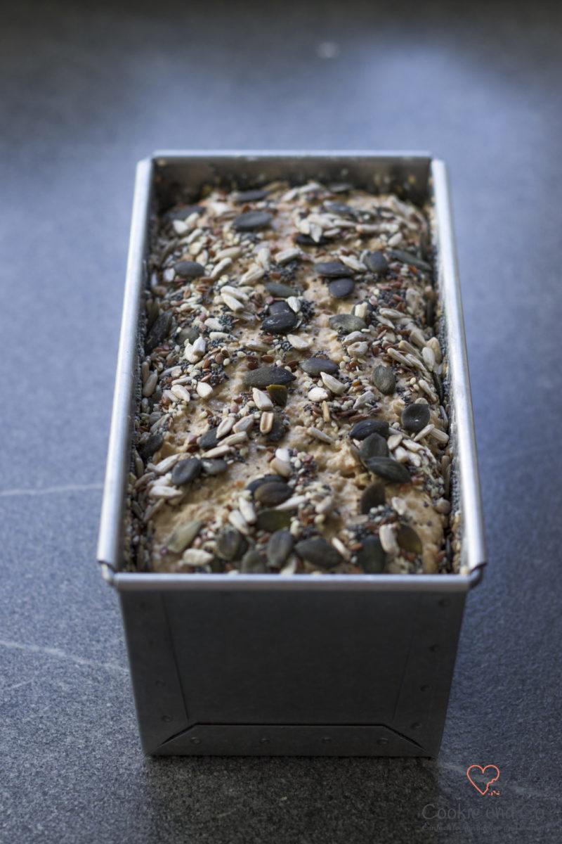 Teig für ein Dinkel-Möhren-Vollkornbrot mit Saaten in einer Kastenform.