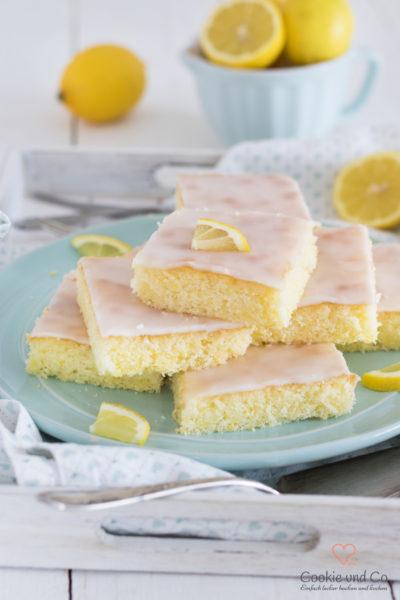 Zitronenkuchen vom Blech auf einem Teller mit Zitrone