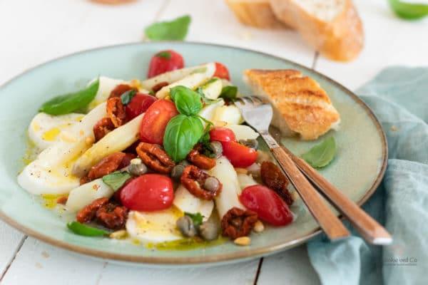Spargelsalat mit Tomaten und Mozzarella auf einem Teller