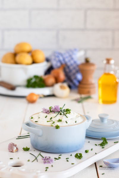 Kräuterquark mit Schnittlauch Petersilie und Schnittlauchblüten. Im Hintergrund Kartoffeln, Leinöl, Zwiebeln und Knoblauch sowie eine Pfeffermühle.