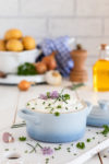 Quark-Dip mit Schnittlauch Petersilie und Schnittlauchblüten. Im Hintergrund Kartoffeln, Leinöl, Zwiebeln und Knoblauch sowie eine Pfeffermühle.