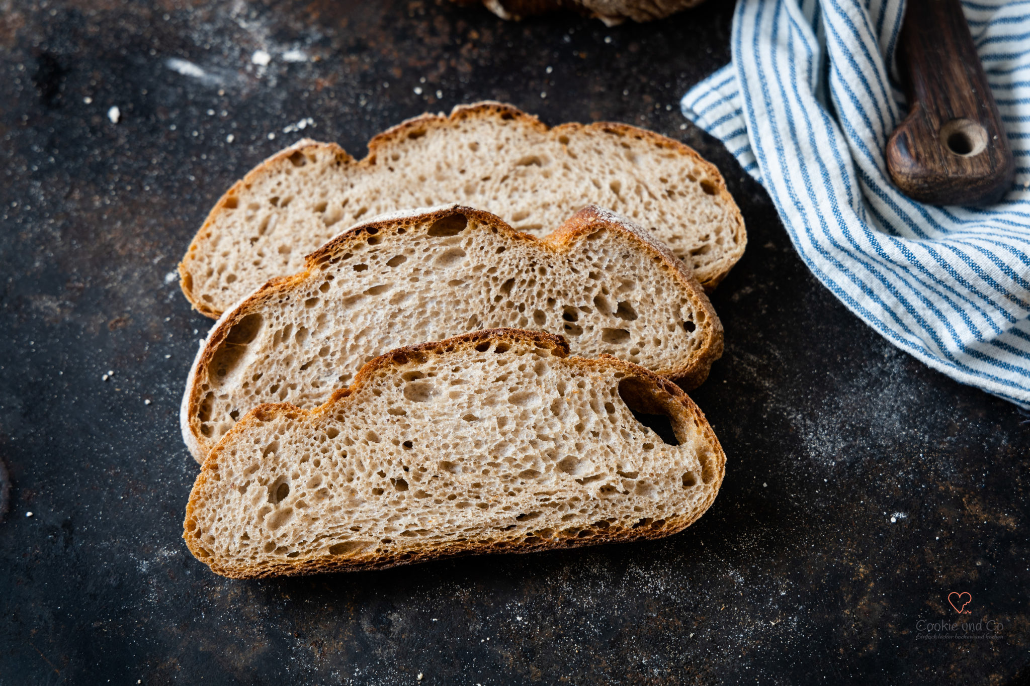 Brotscheiben auf einem alten Backblech von einem Mischbrot mit Weißbier und Sauerteig.