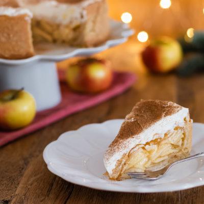 Kuchenstück von einer Apfel-Glögg-Torte (Apfel-Wein-Torte) auf einem Teller mit Weihnachtsbeleuchtung im Hintergrund.
