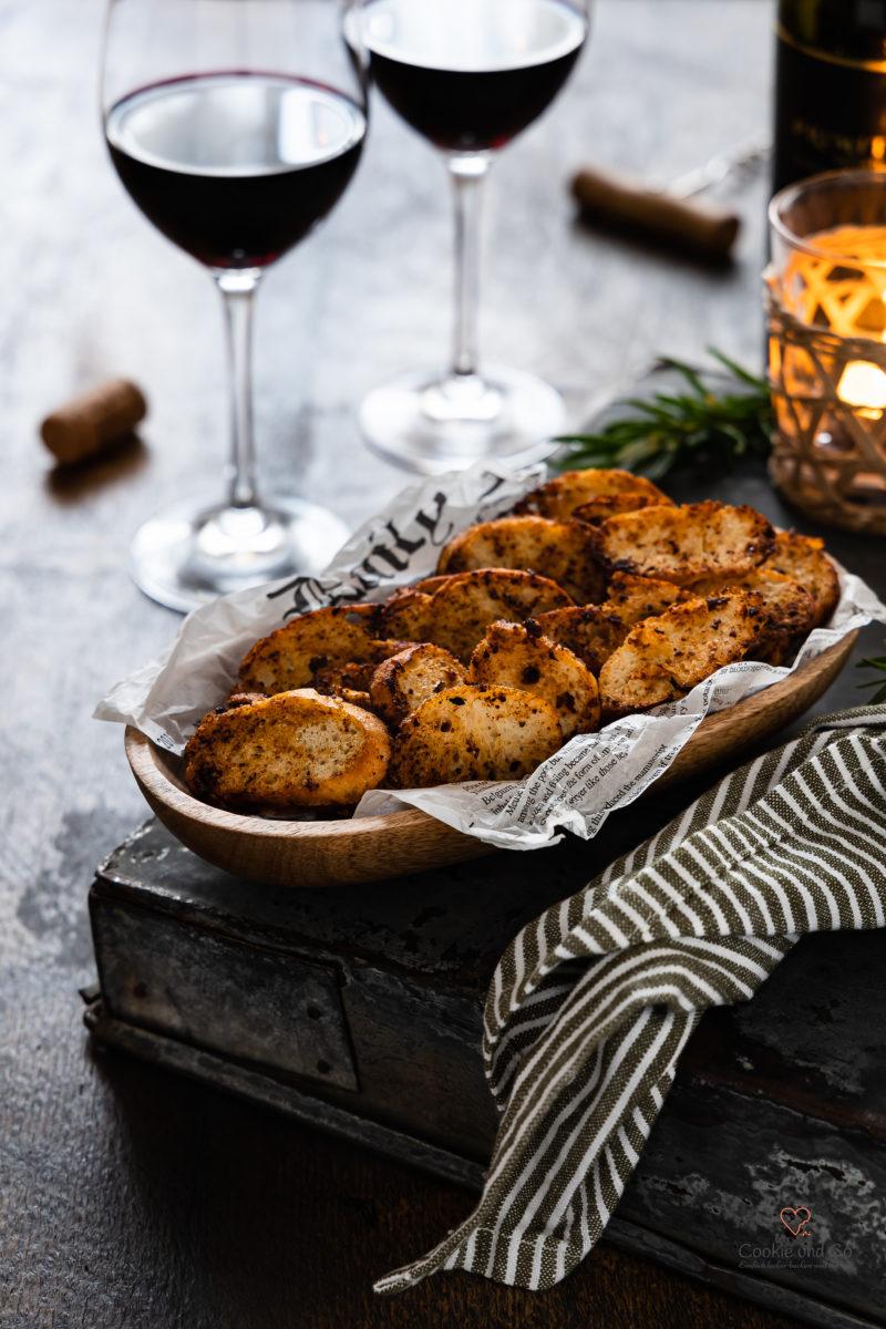 Selbstgemachte Chips aus altbackenem Brot in einer Holzschale mit Rotwein im Hintergrund
