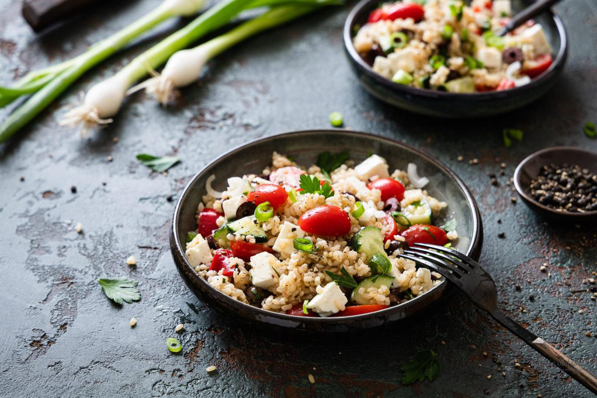 Salat aus Reis griechischer Art mit Tomaten, Gurke und Feta