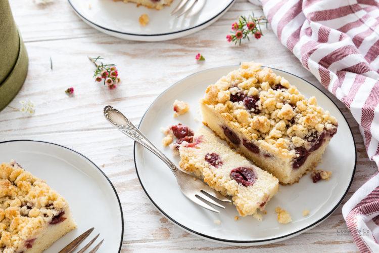 Ein Kirsch-Streuselkuchen auf einem Teller mit einer Gabel und Blumen im Hintergrund (schneller Blechkuchen aus Rührteig)