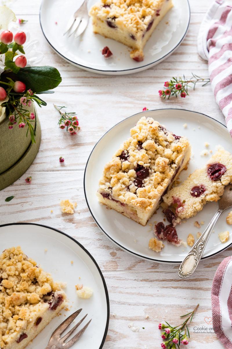 Kirschkuchen mit Streusel verteilt auf einem Tellern und Blumen im Hintergrund (schneller Blechkuchen aus Rührteig)