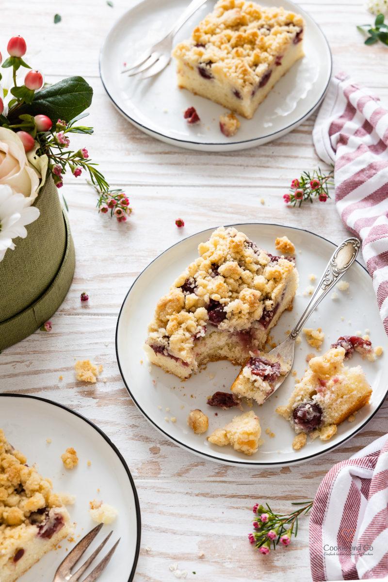 Ein Stück Kirsch-Streuselkuchen auf einem Teller mit einer Gabel und Blumen im Hintergrund (schneller Blechkuchen aus Rührteig)